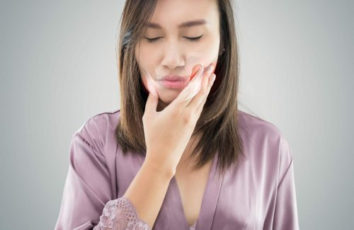 Temporomandibular Joint and Muscle Disorder: TMD, Suffering from toothache. Beautiful young woman suffering from toothache while standing against grey background