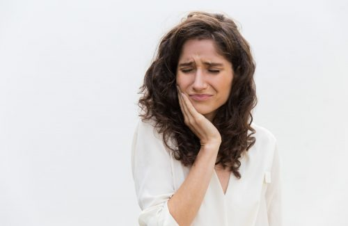 Frustrated unhappy woman suffering from toothache. Wavy haired young woman in casual shirt standing isolated over white background. Dental problem concept